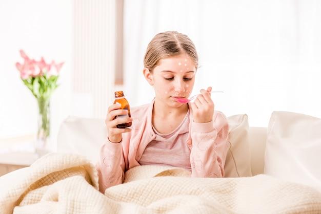 治療するシロップを取っている十代の少女