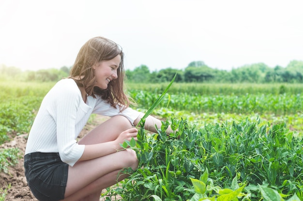 Teen girl touches hands with green plants in the garden