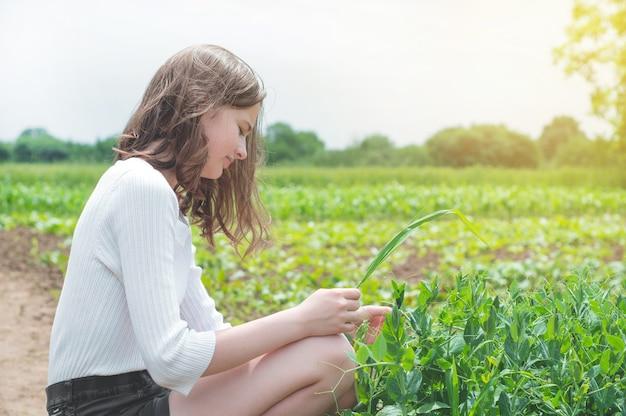 十代の少女は庭の緑の植物で手を触れる