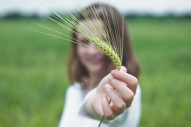 Девушка трогает руки с зелеными растениями в саду