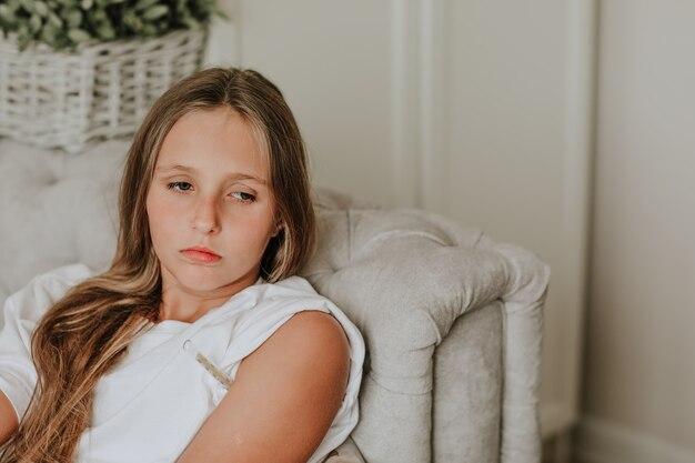Девушка с помощью термометра выглядит очень грустно.