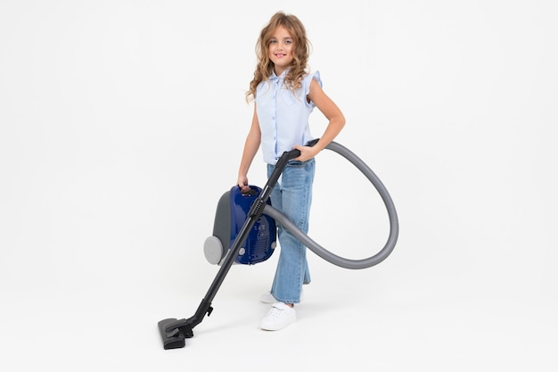 Teen girl vacuuming the floor with a vacuum cleaner on an isolated white background with copy space.