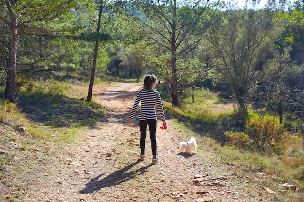 Teen girl walking with a white dog in forest