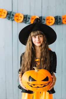 Teen girl in witch costume holding pumpkin