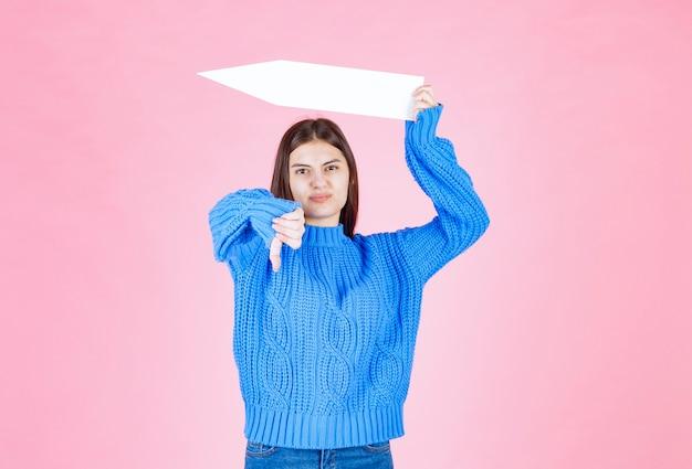 Ragazza teenager con una freccia di carta che mostra un pollice verso il basso.