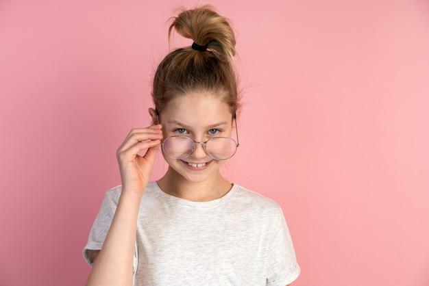Девушка со светлыми волосами носит круглые очки на розовой стене