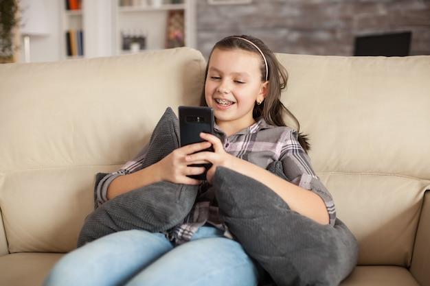スマートフォンでメッセージを書いているリビングルームのソファに座っている中かっこを持つ十代の少女。