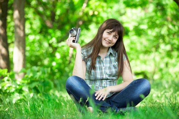 녹색 공원에서 카메라와 함께 십 대 소녀입니다.
