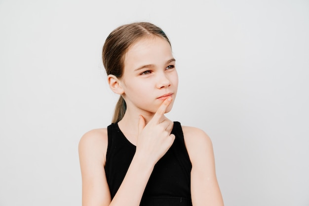 A teen girl with collected hair in a black t-shirt stands on a white background, holds index finger in front of lips and thought. place for the inscription. observe silence.
