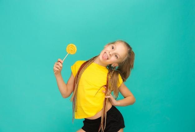 La ragazza teenager con la lecca-lecca variopinta su una parete blu