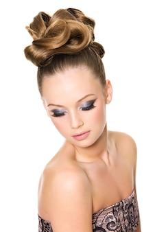 ファッションの巻き毛の髪型と白いスペースでポーズをとって明るいグラマーメイクの10代の少女