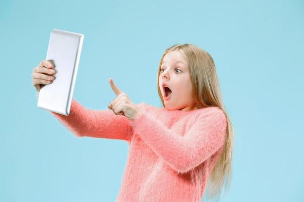 Ragazza teenager con il computer portatile. amore al concetto di computer. ritratto frontale a mezzo busto femminile attraente, backgroud blu alla moda dello studio. emozioni umane, concetto di espressione facciale.