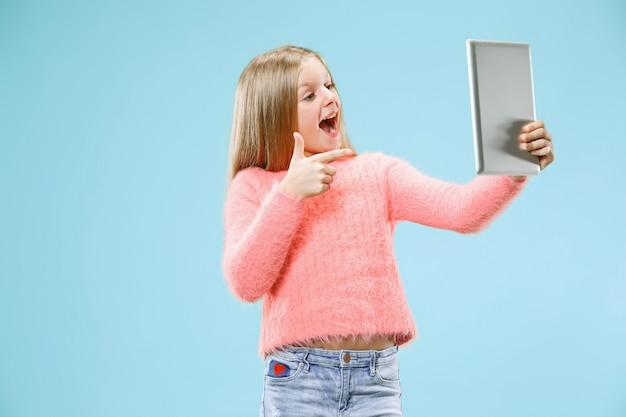 ラップトップを持つ十代の少女。コンピュータの概念が大好きです。魅力的な女性のハーフレングスのフロントポートレート、トレンディな青いスタジオの背景。人間の感情、表情の概念。