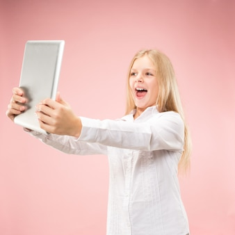 ラップトップを持つ十代の少女。コンピュータの概念が大好きです。魅力的な女性のハーフレングスのフロントポートレート、トレンディなピンクのバックグラウンド