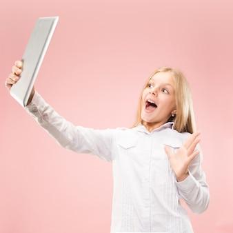 ラップトップを持つ十代の少女。コンピュータの概念が大好きです。魅力的な女性のハーフレングスのフロントポートレート、トレンディなピンクのスタジオバックグラウンド。人間の感情、顔の表情の概念。