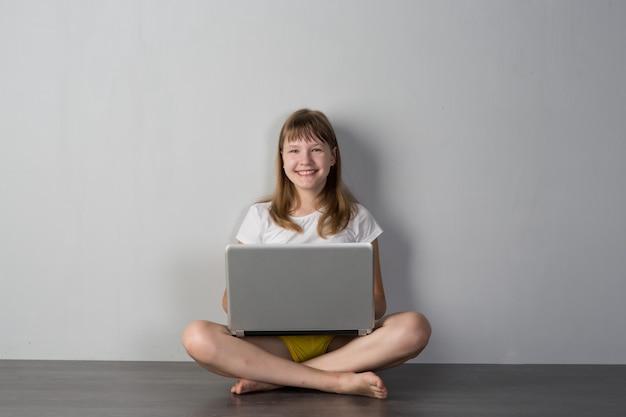 회색 배경에 노트북과 십 대 소녀