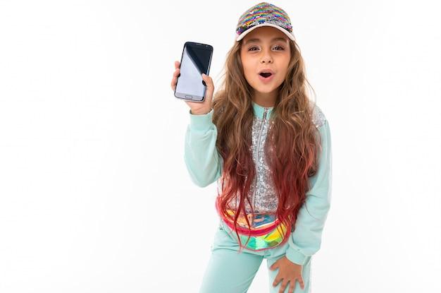 ヒントピンクで染められた長いブロンドの髪を持つ十代の少女、光沢のある白い帽子、水色のスポーツスーツ、ベルトバッグは笑顔で電話を見せます
