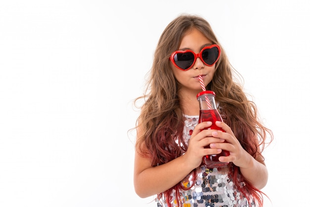 Teen girl with long blonde hair dyed with tips pink, in shiny light dress, black and white sneakers, glasses, standing with headphones, holding juice in glass bottle with striped tube in hand