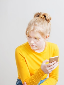 白い表面に携帯電話を持つ十代の少女
