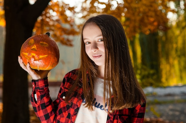 A teen girl with a smile holding a pumpkin