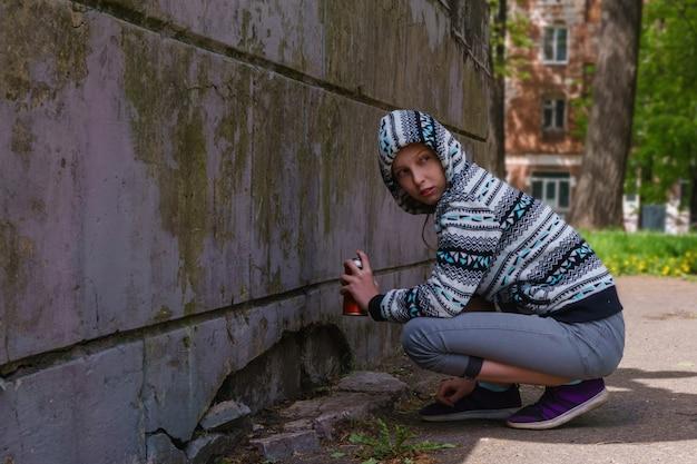 스프레이 페인트를 칠한 10대 소녀가 주위를 둘러보고 벽에 낙서를 쓰려고 합니다.
