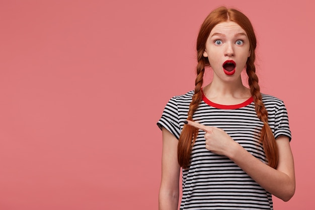 Девушка-подросток с двумя рыжими косичками, красная помада, широко открыла рот в панике, потрясенный, обеспокоенный указательный палец слева привлекает ваше внимание, чтобы скопировать пространство над розовой стеной