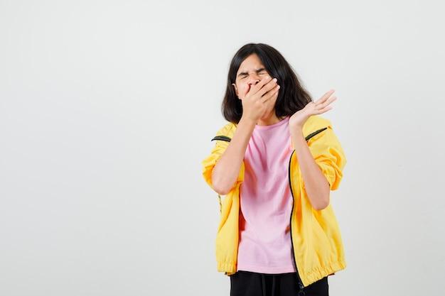 Ragazza teenager che sbadiglia, allarga il palmo della mano in maglietta, giacca e sembra assonnata. vista frontale.