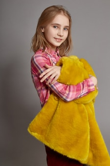 Teen girl in yellow faux fur coat, portrait