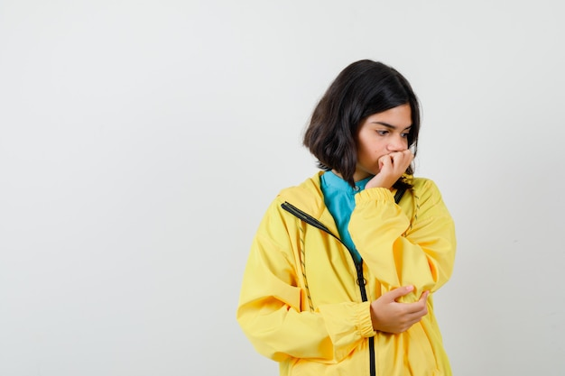 Ragazza teenager in giacca gialla che pensa a qualcosa, guarda in basso e sembra triste, vista frontale.