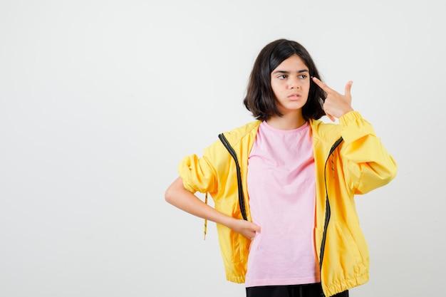 Ragazza teenager in tuta gialla, t-shirt che punta alle tempie con il dito e sembra insoddisfatta, vista frontale.