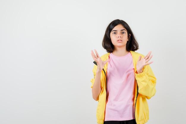 Ragazza teenager in tuta da ginnastica gialla, t-shirt allargando le palme e guardando scioccata, vista frontale.