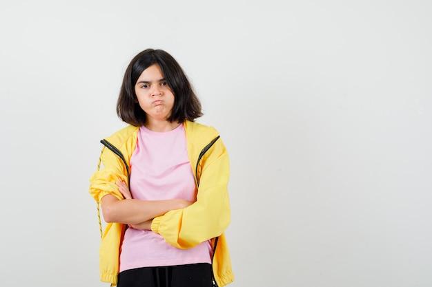 Ragazza teenager in tuta gialla, t-shirt in piedi con le braccia incrociate, le guance gonfie e l'aria insoddisfatta, vista frontale.