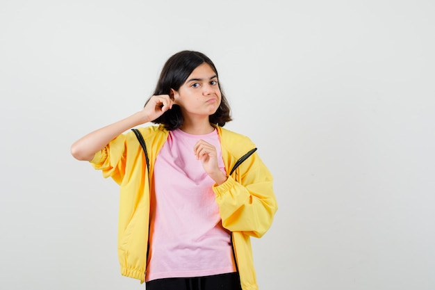 Teen girl in yellow tracksuit, t-shirt standing with pulling ear down and looking displeased , front view.