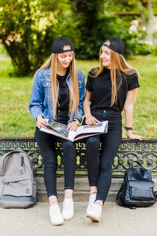 Teen girls discussing book in park