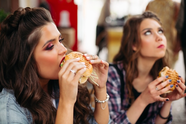 Teen girls enjoying burgers in cafe.