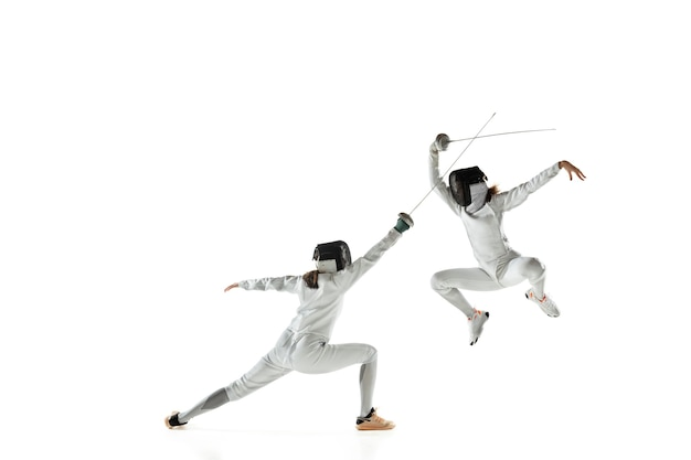 Ragazze adolescenti in costumi di scherma con le spade nelle mani isolate su sfondo bianco studio. giovani modelli femminili che praticano e si allenano in movimento, azione. copyspace. sport, gioventù, stile di vita sano.
