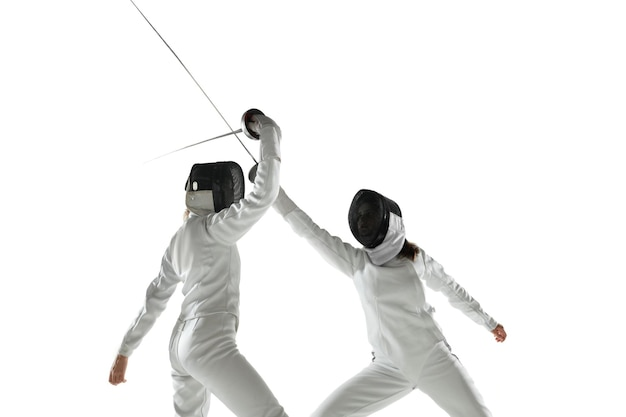 Teen girls in fencing costumes with swords in hands isolated on white studio background. young female models practicing and training in motion, action. copyspace.