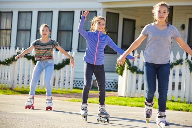 Teen girls group rolling skate in the street