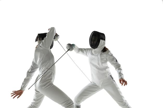 白いスタジオの背景に分離された手に剣でフェンシングの衣装を着た10代の女の子。動き、行動の練習とトレーニングをしている若い女性モデル。コピースペース。スポーツ、若者、健康的なライフスタイル。 無料写真