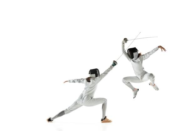 흰색 스튜디오 배경에 고립 된 손에 칼을 가진 펜싱 의상에서 십 대 소녀. 젊은 여성 모델 연습 및 운동, 행동 훈련. copyspace. 스포츠, 젊음, 건강한 라이프 스타일.