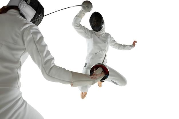 白いスタジオの背景に分離された手に剣でフェンシングの衣装を着た10代の女の子。動き、行動の練習とトレーニングをしている若い女性モデル。コピースペース。スポーツ、若者、健康的なライフスタイル。