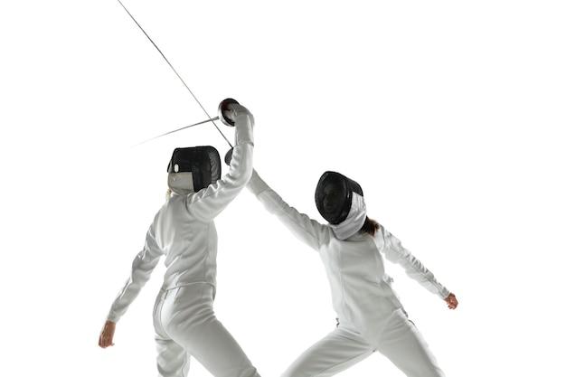 흰색 스튜디오 배경에 고립 된 손에 칼으로 펜싱 의상에서 십 대 소녀. 젊은 여성 모델 연습 및 운동, 행동 훈련. copyspace.