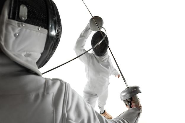 白いスタジオの背景に分離された手に剣でフェンシングの衣装を着た10代の女の子。動き、行動の練習とトレーニングをしている若い女性モデル。コピースペース。