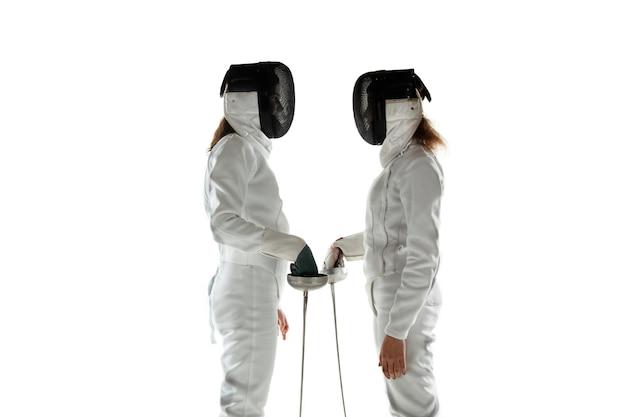 白いスタジオの背景に分離された手に剣でフェンシングの衣装を着た10代の女の子。若い女性モデルのトレーニング、自信を持ってポーズ。コピースペース。モーション、アクション。