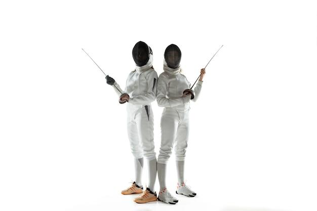 白いスタジオの背景に分離された手に剣でフェンシングの衣装を着た10代の女の子。若い女性モデルのトレーニング、自信を持ってポーズ。コピースペース。スポーツ、若者、健康的なライフスタイル、運動、行動。