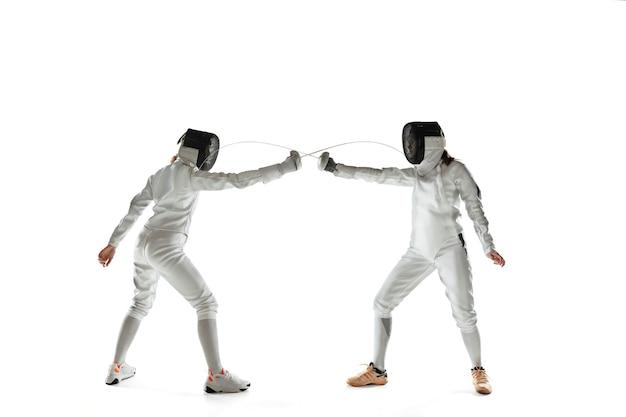 白いスタジオの壁に隔離された手に剣でフェンシングの衣装を着た10代の女の子