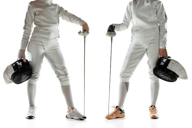 白い壁に剣を手にフェンシングの衣装を着た10代の女の子