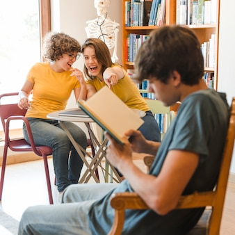 Teen girls laughing and pointing at reading boy