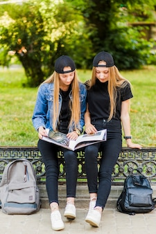 Teen girls reading book on fence