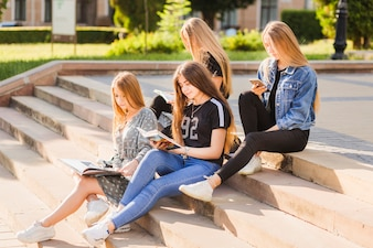 Teen girls reading books and using smartphone on steps